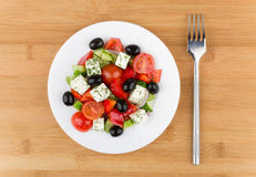 Glass plate with Greek salad and fork on bamboo table Royalty Free Stock Photography