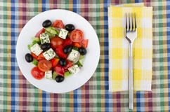Glass plate with Greek salad and fork on table Royalty Free Stock Photo