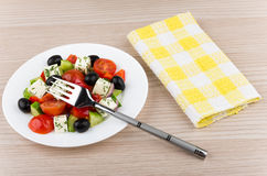 Glass plate with Greek salad, napkin and fork Stock Photo