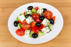 Glass plate with Greek salad on table Stock Images
