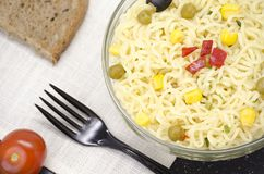 Glass plate of noodles, fork, bread and tomato royalty free stock photography