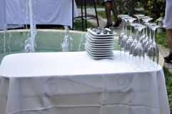 GLASS PLATE AND RECEPTION. Stemware Morgon and saucers breakable exposed near a water jet fountain that is an important link in the success of a wedding stock photo