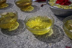 Glass plates with oil and yellow and red flowers royalty free stock photo