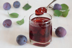 Glass with plum jam. Plum jam in a glass, spoon, plums Stock Images