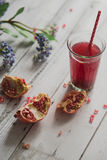 Glass of pomegranate juice with fresh fruits on wooden table Royalty Free Stock Photos