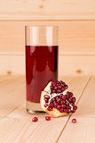 Glass of pomegranate juice and grains on wood. Royalty Free Stock Images