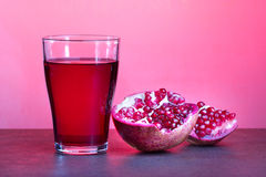 A glass of pomegranate juice with pomegranate fruits on wooden table. Healthy drink concept. Royalty Free Stock Image