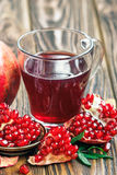 Glass of pomegranate juice with ripe fresh punica granatum fruits with leaves on wooden table Royalty Free Stock Images