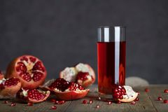 Glass of pomegranate juice on a wooden surface. Closeup royalty free stock photo