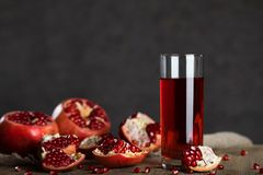 Glass of pomegranate juice on a wooden surface. Closeup royalty free stock photography