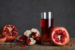 Glass of pomegranate juice on a wooden surface. Closeup royalty free stock photos