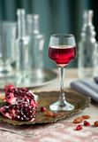 A glass of pomegranate liqueur on the table with grenades. stock photo