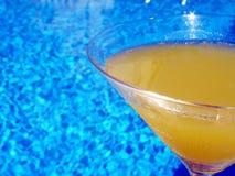 Glass on pool edge. Glass of orange juice on pool edge Royalty Free Stock Photography