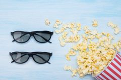glass of popcorn scattered on a blue background, next to glasses, for a three-dimensional view of the film royalty free stock photos