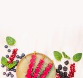 Glass poppar i platta med sommarbär: röd vinbär, björnbär, blåbär och pepparmintsidor på den vita träbackgroen Fotografering för Bildbyråer