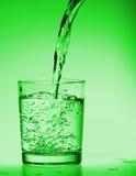 glass poring vatten för drink arkivfoto