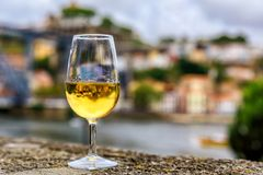 Glass of port wine with the blurred cityscape of Porto Portugal in the background Royalty Free Stock Photography