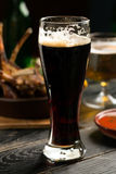Glass of porter beer. On the black table Royalty Free Stock Image