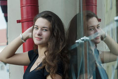 Glass portrait of daydreaming attractive brunette girl posing near glass display window with symmetry reflection Stock Photo