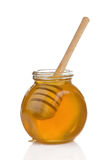 Glass pot full of honey and stick Royalty Free Stock Image