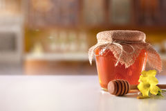 Glass pot with honey and dipper on white kitchen table Stock Image