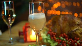 Christmas table setting with turkey. In the glass pour champagne next to the fried bird on a plate with a salad on the table on a background of yellow electric stock footage