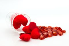 A glass pouring red heart scattered on a white background, using as valentine`s day concept stock photos