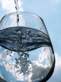 Glass of pouring water with reflection Stock Photography