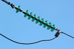 Glass powerline insulator disks against blue sky background Royalty Free Stock Image