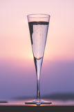 Glass of prosecco at a wooden pier at sunset. Luxury resort vaca Royalty Free Stock Photo