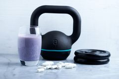 Glass of Protein Shake with milk and blueberries. Creatine capsules, black sporting kettlebell and plates in background. Sport nut. Rition. Stone / Wooden royalty free stock photography
