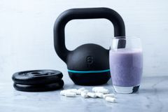 Glass of Protein Shake with milk and blueberries. Creatine capsules, black sporting kettlebell and plates in background. Sport nut. Rition. Stone / Wooden royalty free stock image