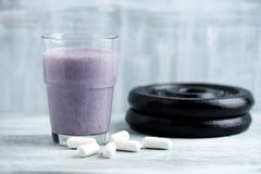 Glass of Protein Shake with milk and blueberries. Creatine capsules and plates in background. Sport nutrition. Rustic wooden background. Copy space royalty free stock photography