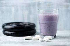 Glass of Protein Shake with milk and blueberries. Creatine capsules and plates in background. Sport nutrition. Rustic wooden background. Copy space royalty free stock photo