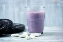Glass of Protein Shake with milk and blueberries. Creatine capsules and plates in background. Sport nutrition. Rustic Wooden background. Copy space stock images
