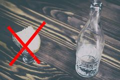 a glass of pure alcohol, a bottle and a piece of bread and cheese on a wooden background. a glass and on it a red cross. concept royalty free stock photo