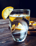 Glass of pure mineral water with lemon on wooden table. Glass of pure mineral water with ripe lemon Royalty Free Stock Photography