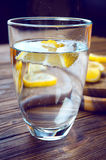 Glass of pure mineral water with lemon on wooden table. Glass of pure mineral water with ripe lemon Royalty Free Stock Images
