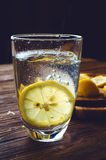 Glass of pure mineral water with lemon on wooden table. Glass of pure mineral water with ripe lemon Royalty Free Stock Photo
