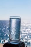 A glass of pure sparkling water. A glass of pure sparkling water against the blue sea and sky Stock Image