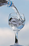 Glass of pure water. Glass in which flows pure water from a bottle royalty free stock photo