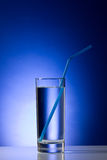 Glass with pure water with a straw on a blue Royalty Free Stock Photos