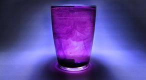 Glass of purple water stock photography