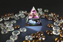 Glass pyramid av yin yang med kulöra glass stenar royaltyfri foto