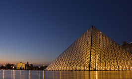 Glass pyramid of Louvre at night. PARIS,FRANCE - NOVEMBER 06: Entrance to Louvre Museum and Arc de Triomphe du Carrousel on November 06, 2012 in Paris. The Royalty Free Stock Photo