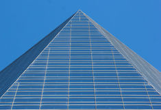Glass pyramid top of a skyscraper against blue sky background Royalty Free Stock Photo