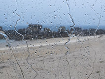 Glass with raindrops. In transparent view of beach on the sea Stock Photos