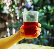Glass with raspberry juice in hand Stock Photography