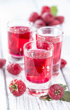 Glass with Raspberry Liqueur. And some fresh fruits Stock Photo