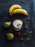 Glass of raspberry and pear smoothie with fresh mint leaves on black. Backdrop Stock Photography